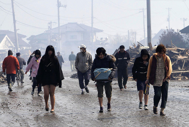 People walk on a muddy road as they evacuate to a shelter in Natori city